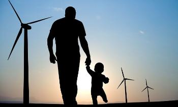 A tall man holding av small kid walkning in the sunrise towards som wind mills.