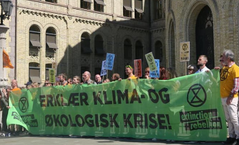 Protesters from Exctinction Rebellion holding a banner outside the Norwegian parliament