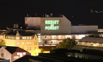 "photograph of an urban landscape with a large neonlit sign spelling ""resist forest"" on a building, night time"