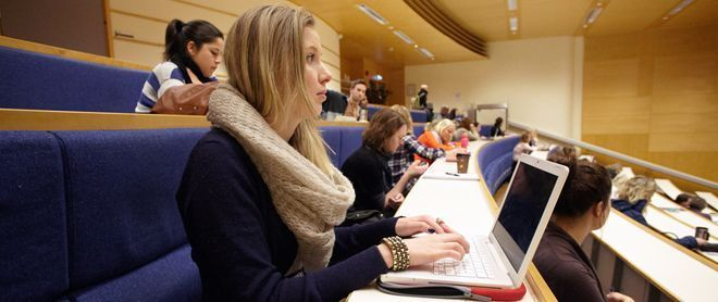 Female student with a lap top in lecture hall. Photo.