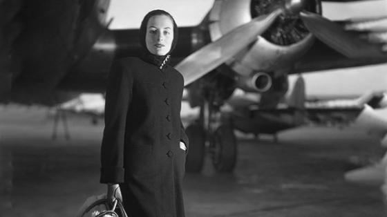 Black and White photo of stylish woman standing in front of an airplane.