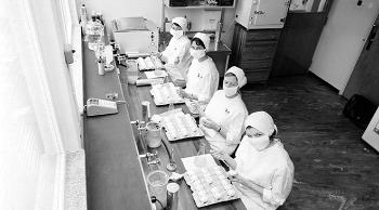 Historical photo of masked women working in a large labarotory