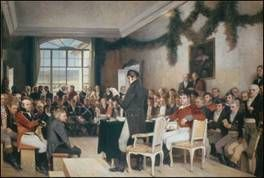 A man standing and talking in a nice room with other nice dresses men listening.