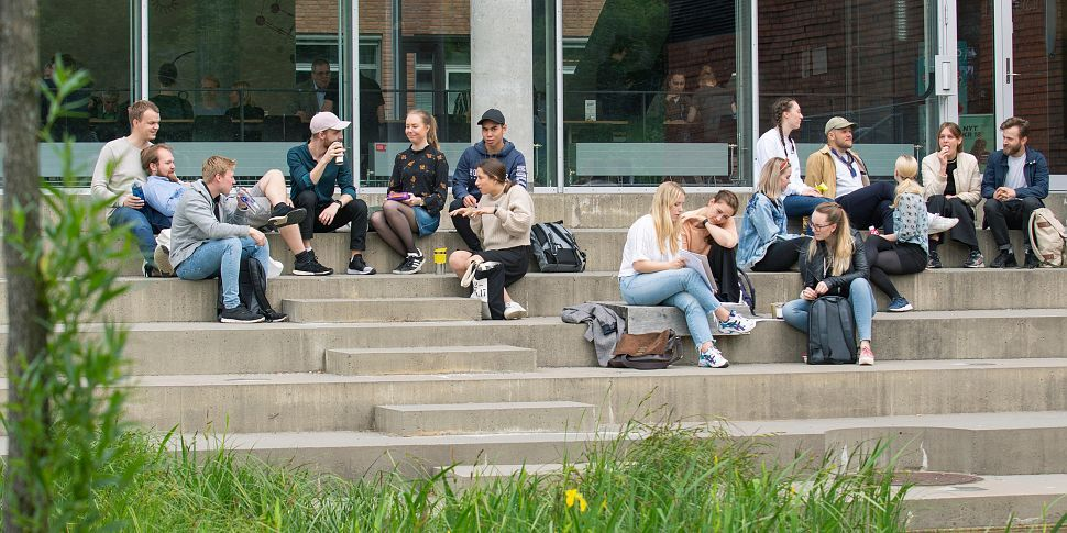 Students relaxing on the steps in front of a University building