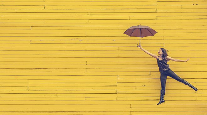 Woman with umbrella floating before a yellow wall