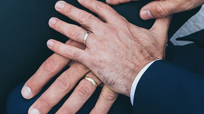 Two male hands wearing wedding rings.