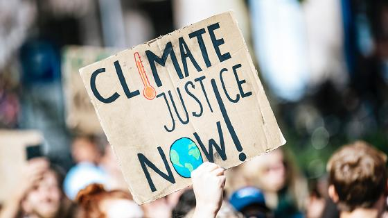 """Climate demonstrators holding a poster with the text: """"Climate justice now"""". Photo."""
