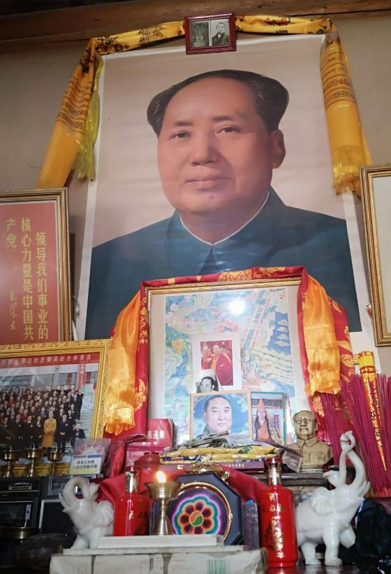 Big portrait of a man and many things around like light, pictures, Dalai Lama. Photo.