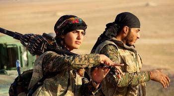 Kurdish YPG-soldiers in Rojava. A woman with military gear and weapon, a man in the background.