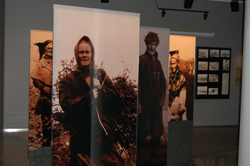 Exhibiton with photos of people, an old woman working outside in front.