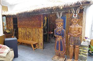 To skulpturer foran en hytte.