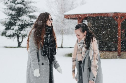 Two women having a conversation in snowy weather