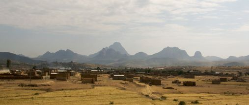 Houses on brown ground in front and tall mountains in the skyline.