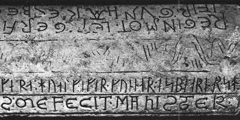 Runes and latin letters carved on a stone.
