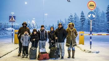 Seven people standing in a road. Men, women and children with bags. Wintertime.