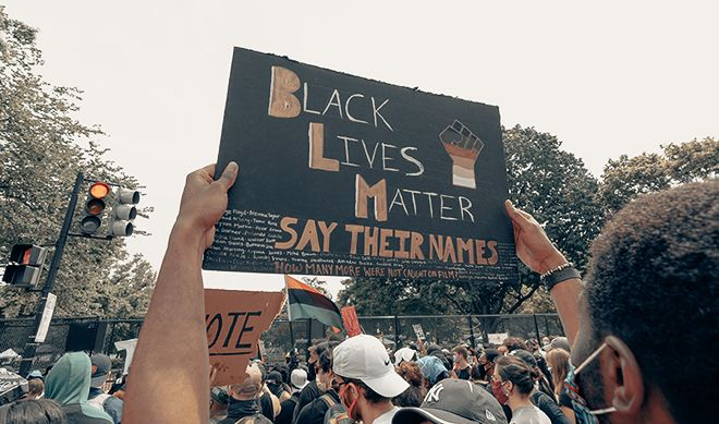 "Demonstration. Banner saying ""Black lives matter. Say their names""."