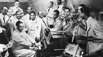 Duke Ellington at the piano, surrounded by orchestra players