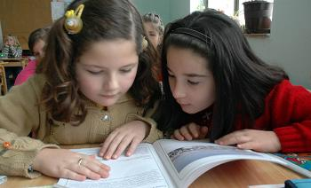 Two girls reading a book together.