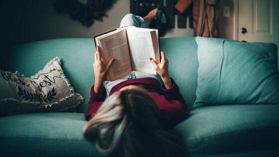 Kvinne leser bok på sofa.