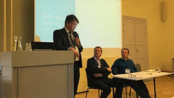 Professor Geir Flikke står i midten av bildet med en mikrofon og snakker ut til et publikum som er utenfor bildet. Bak ham er det en presentasjon. Til høyre for ham ser to kollegaer opp mens han snakker.