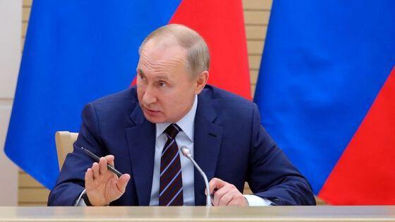 President Vladimir Putin snakker, har russiske flagg bak ham.