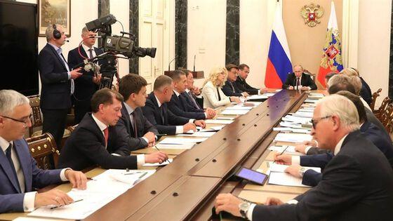 Russlands president Vladimir Putin sitter i enden av et stort konferansebord, i et møte med Russlands regjeringsmedlemmer.