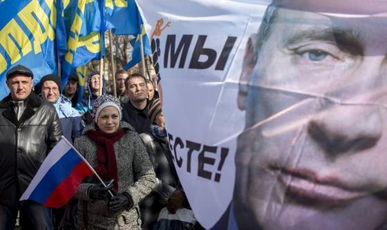 Folk protesterer mot Putin. En dame holder et russisk flagg, og et banner av Putin med slagord mot ham flyr i vinden.