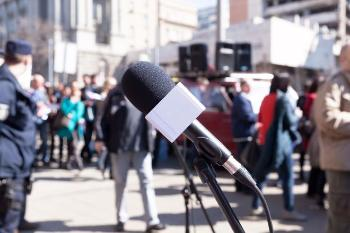 A microphone and crowd protesting on the street
