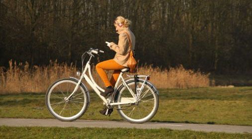 Woman bicycling and looking at her mobile.