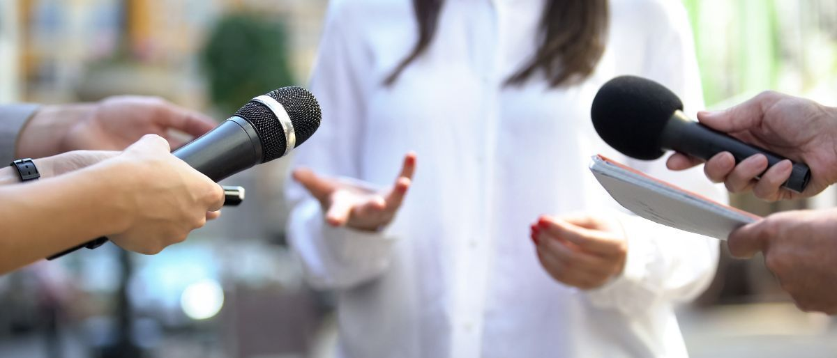 A woman in a white shirt is being interviewed by many journalists.