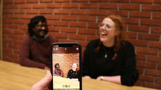 Bilde av Rajeev Sharma Busgeeth og Hanna Marie Nicholas sett gjennom en mobilskjerm, de sitter ved et bord og smiler og ler.