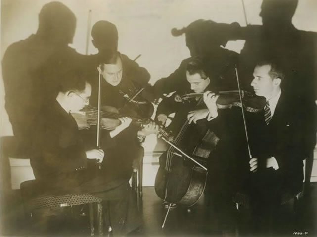 Four men play on violin, cello among and more instruments. Photo.