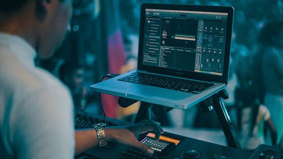 En mann spiller musikk med et keyboard og en laptop.