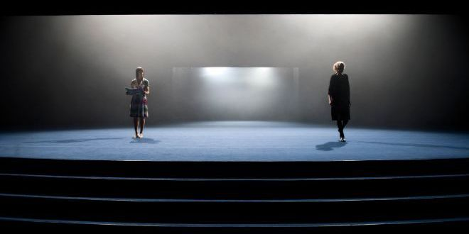 A dark stage with two figures, each standing symmetrically with a doorway between them.