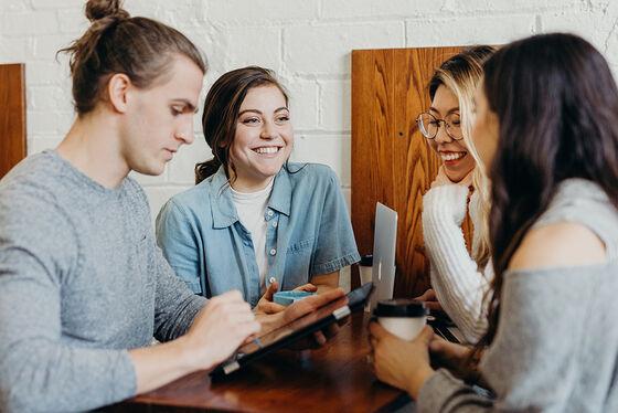 En ung mann og tre unge kvinner sitter rundt et bord og snakker. Mannen sitter med et nettbrett og den ene kvinnen har en laptop. De to andre kvinnene sitter med kaffekopper.