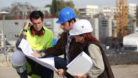 To mannlige bygningsarbeidere og en kvinne med hjelm ser på et kart eller dokument.
