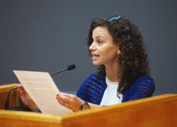 Kellie Gonçalves speaking at the podium