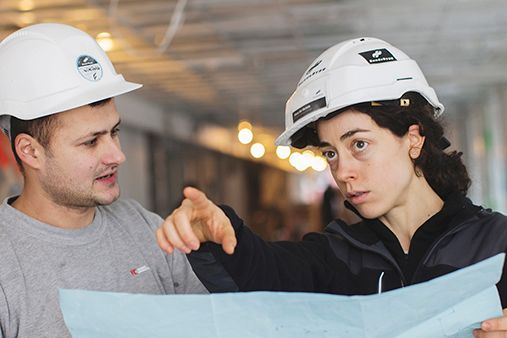 A man and a woman with building construction helmets. And the woman is pointing.