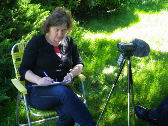 Janne Bondi Johannessen, a white woman in her 50s in jeans and a black cardigan, sits on a lawn on a green garden chair taking notes on a pad