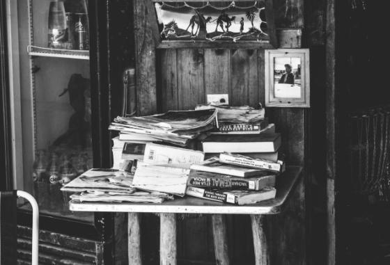 Stack of books on a table, black and white image.