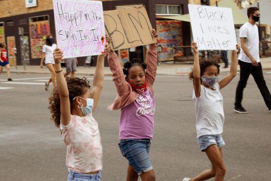 Tre unge jenter med munnbind går i demonstrasjonstog for Black Lives Matter