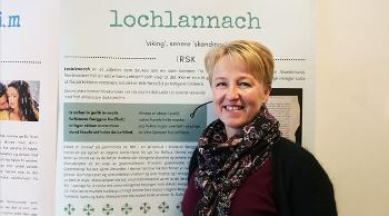 Kristin Bech foran en plakat med påskriften «Lochlannach».
