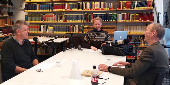 Erling Sandmo, Anders Brenna og Thomas Hylland Eriksen rundt et bord med mikrofoner.