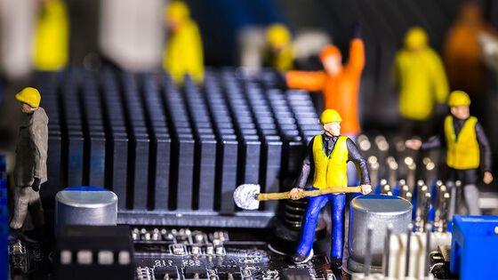 Små figurer kledd som bygningsarbeideer jobber med et kretskort