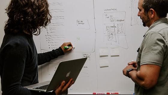 Bilde av kvinne og mann som skriver på whiteboard, sett bakfra.