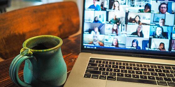 Fotografi av en laptop med bilder fra et web-møte, en blå kaffekopp i forgrunnen.