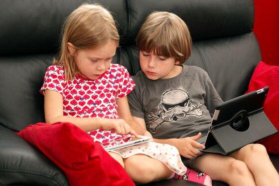 To barn som ser på hver sin skjerm.