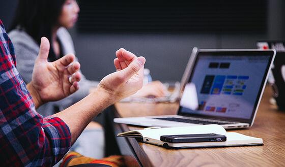 En mann gestikulerer med hender foran laptop og kvinne.